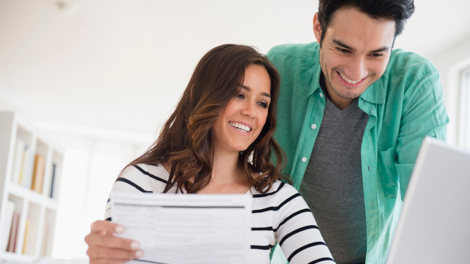 Happy young couple looking at their finances