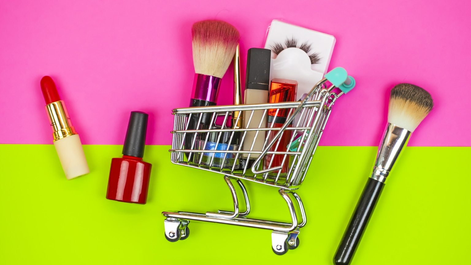 Grocery cart with makeup on pink and lime green background