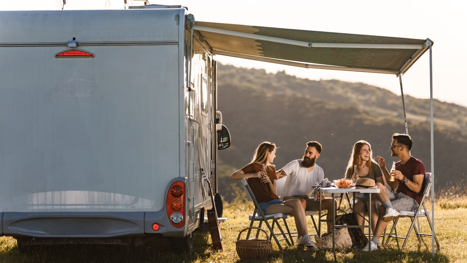 Group Of Friends Eating Outside Of RV
